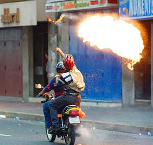 man on a motorcycle throwing a Molotov cocktail