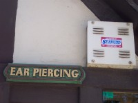 a sign stating 'ear piercing' next to an alarm box