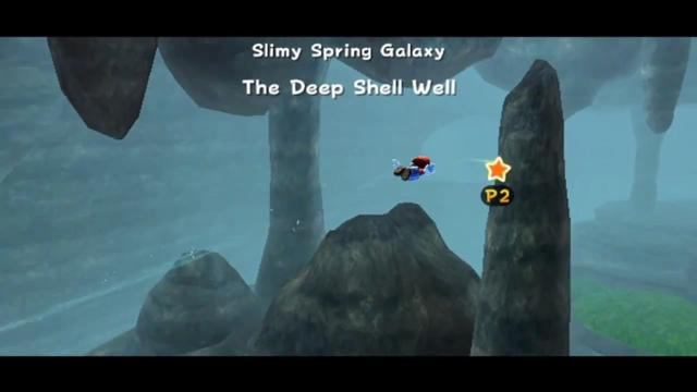 Mario flying through a dank cave, foggy with rocks and a small bit of vegetation.